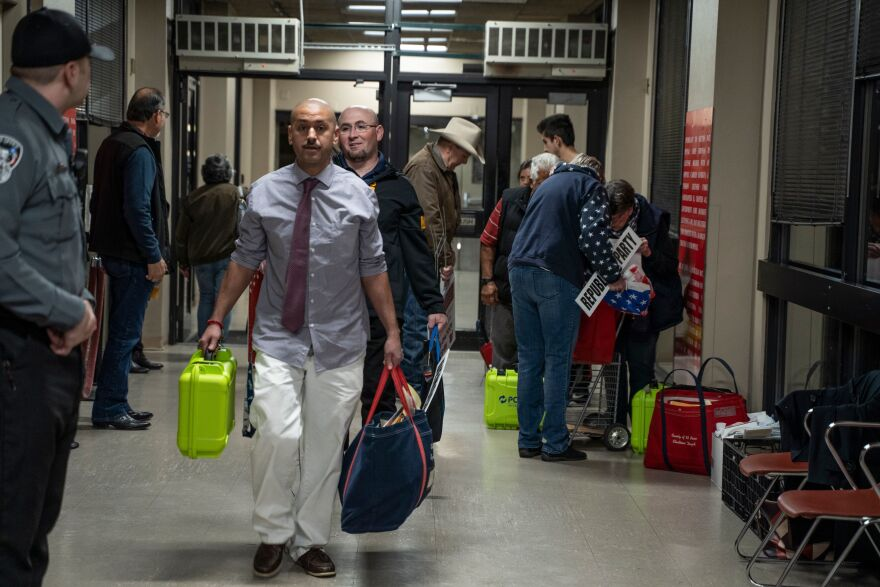 Election officials carrying equipment during last month's presidential primary in El Paso. A Texas judge says he will allow all voters to apply for absentee ballots in light of the coronavirus pandemic. The state typically makes it difficult to cast such ballots.