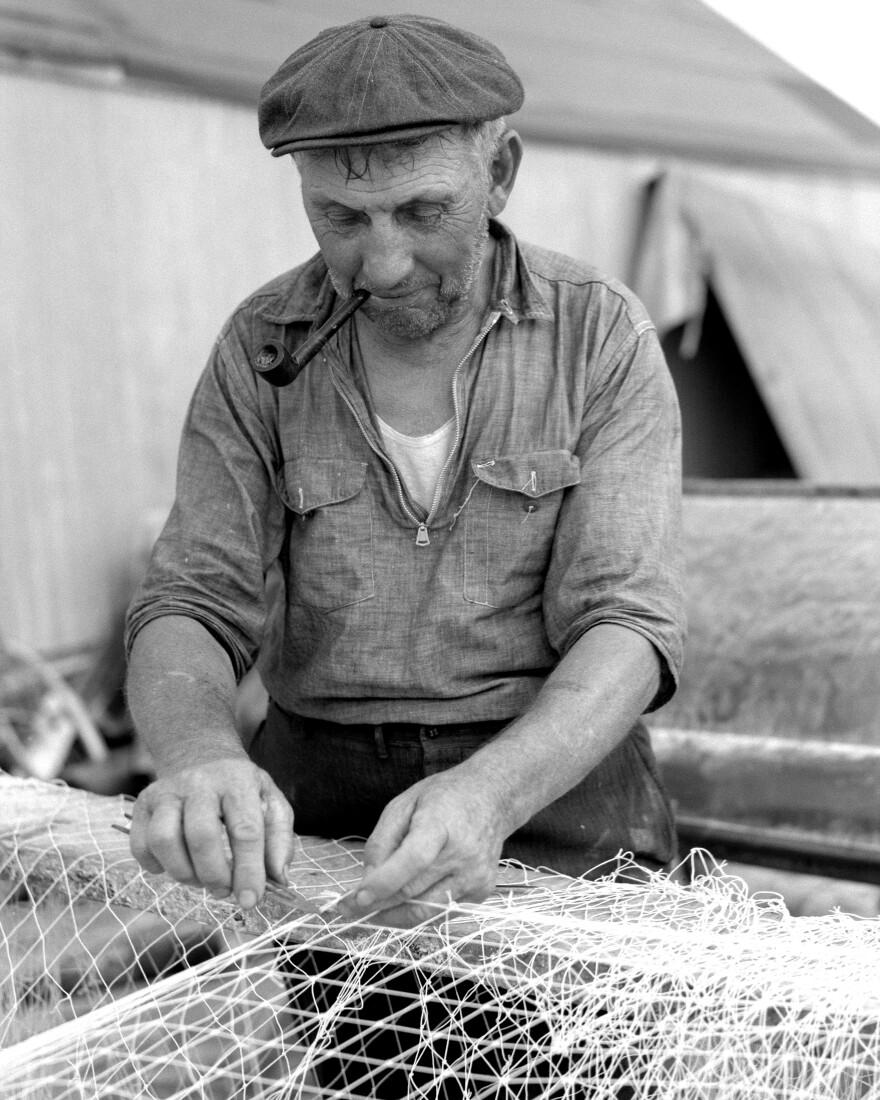 fisherman_with_pipe_repairing_his_net_8b36344a_0.jpg