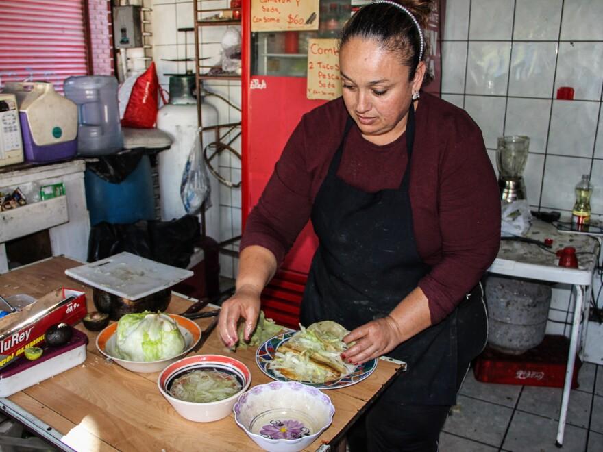 Elvia Gonzalez makes <em>tacos dorados</em> (crispy, fried tacos) for a customer.
