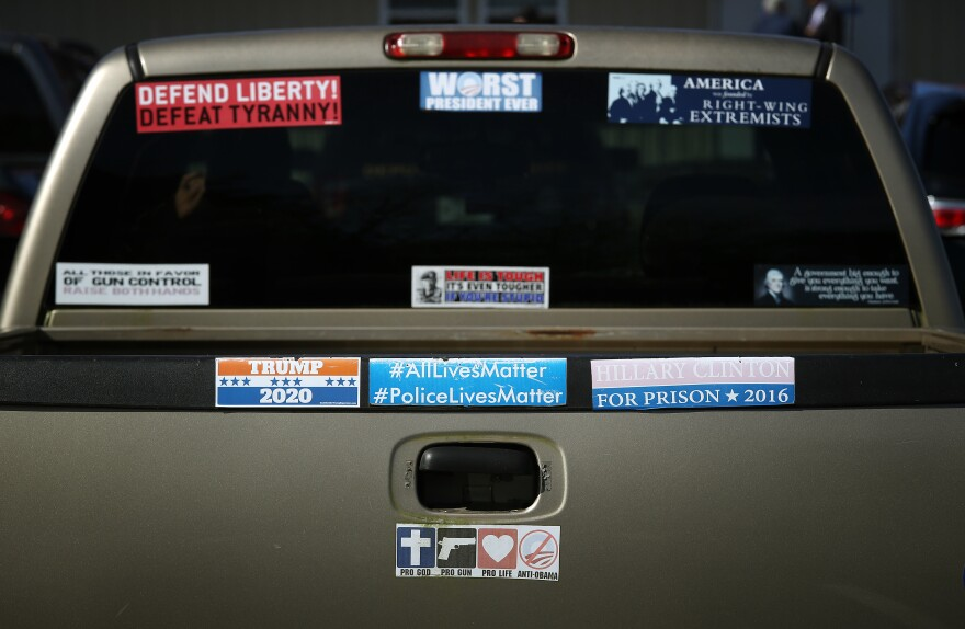 A pickup truck decorated with conservative- and Trump-supporting bumper stickers sits at a Republican campaign event in 2018. On Saturday, conservative political analyst Shermichael Singleton wonders where he fits in that party.