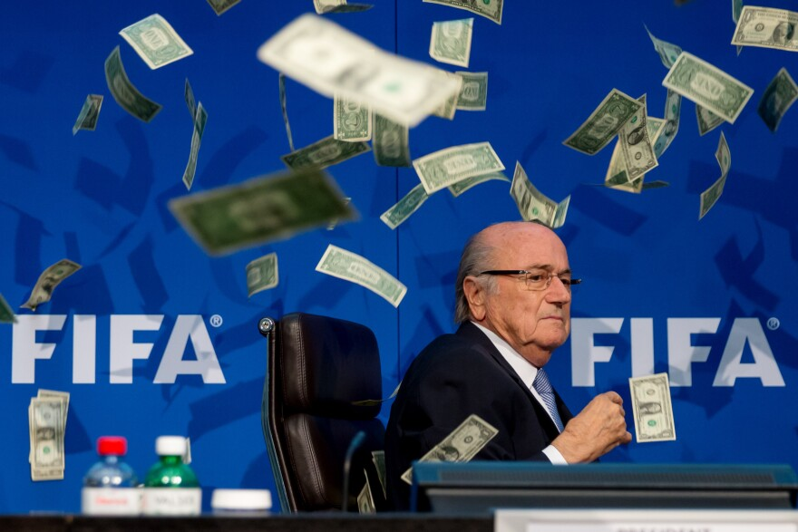Comedian Simon Brodkin throws cash at FIFA President Joseph S. Blatter during a press conference at the Extraordinary FIFA Executive Committee Meeting at the FIFA headquarters on Monday in Zurich, Switzerland.