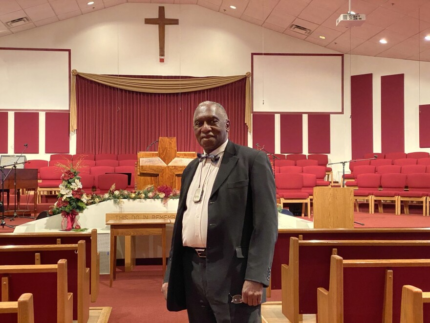 A pastor stands in an empty church