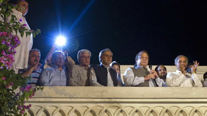 Former Prime Minister Nawaz Sharif, second from right, declares victory in Pakistan's general elections, as his brother Shahbaz Sharif, right, and others listen at the party's headquarters in Lahore.