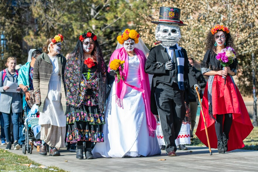 Costumed marchers lead a parade through campus.