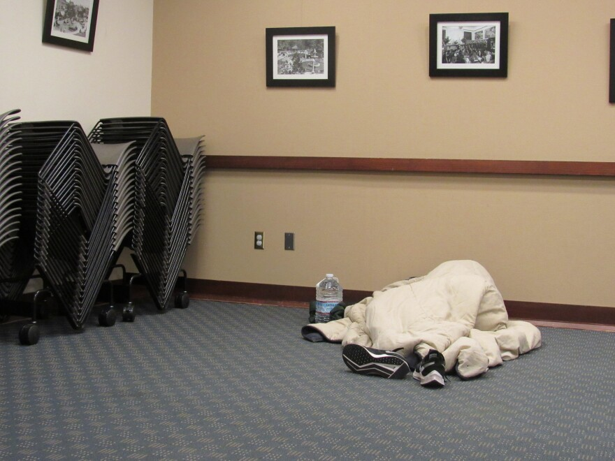 A person sleeps on the floor at an emergency warming shelter at the Ashland Public Library on Tuesday night.