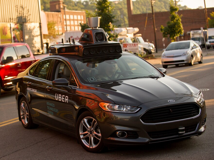 An Uber driverless Ford Fusion drives in Pittsburgh in 2016. On Friday, Uber and Google's Waymo self-driving unit announced a settlement in their trade secrets case.