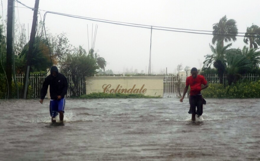 Residents wade through a street flooded with water brought on by Hurricane Dorian in Freeport, Bahamas, on Tuesday. The storm spent most of Monday and into the morning Tuesday essentially stalled out over the Bahamas, relentlessly pounding the islands with high winds and catastrophic flooding.