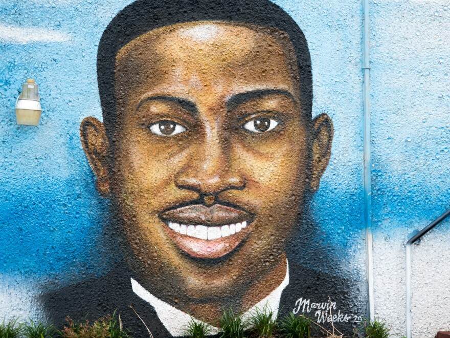 "A mural depicting Ahmaud Arbery in July 2020 in Brunswick, Ga. Gregory McMichael, Travis McMichael, and William ""Roddie"" Bryan are facing murder charges in connection with his death."