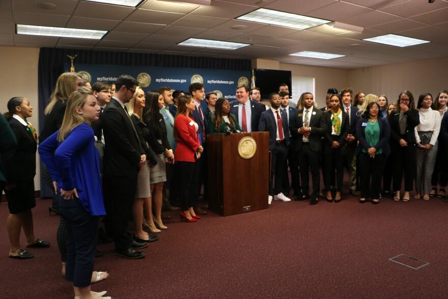 College students crowd around podium.