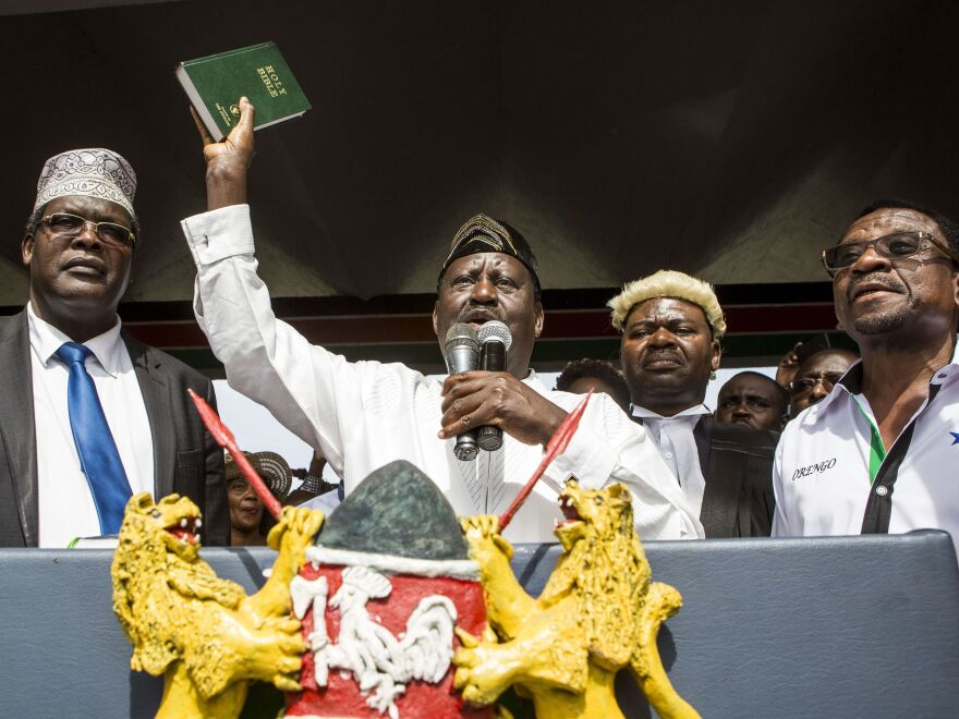 "Kenya's opposition leader Raila Odinga holds up a Bible as he swears himself in as the ""people's president"" on Tuesday in Nairobi. Authorities shut the top three independent TV channels ahead of the event. They remain closed."