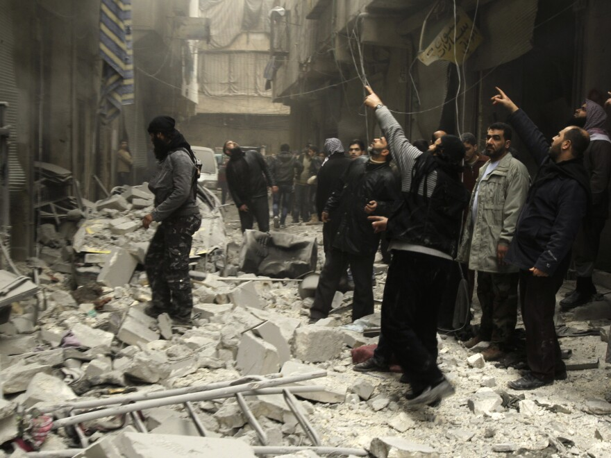 Syrian look up after an apparent airstrike by forces loyal to President Bashar Assad on Tuesday in the city of Aleppo.