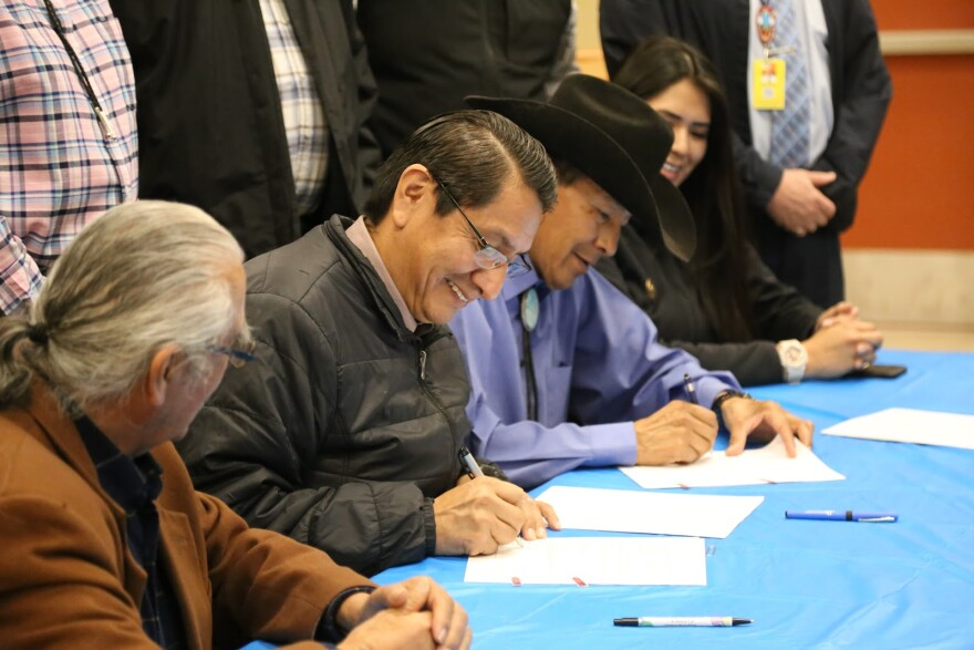 Photo of three men and a woman sitting at a table smiling and signing papers