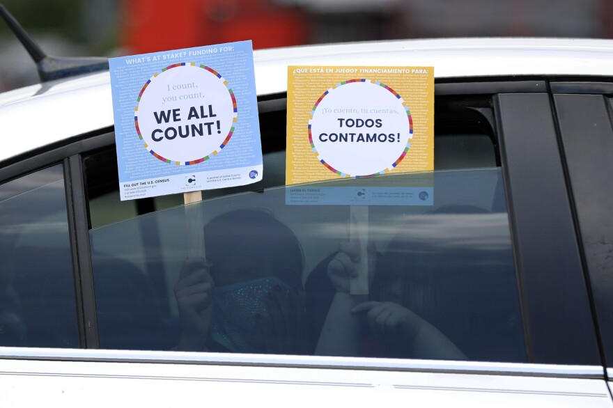In this June 25, 2020, file photo, two young children hold signs through the car window that make reference to the 2020 U.S. Census as they wait in the car with their family at an outreach event in Dallas.
