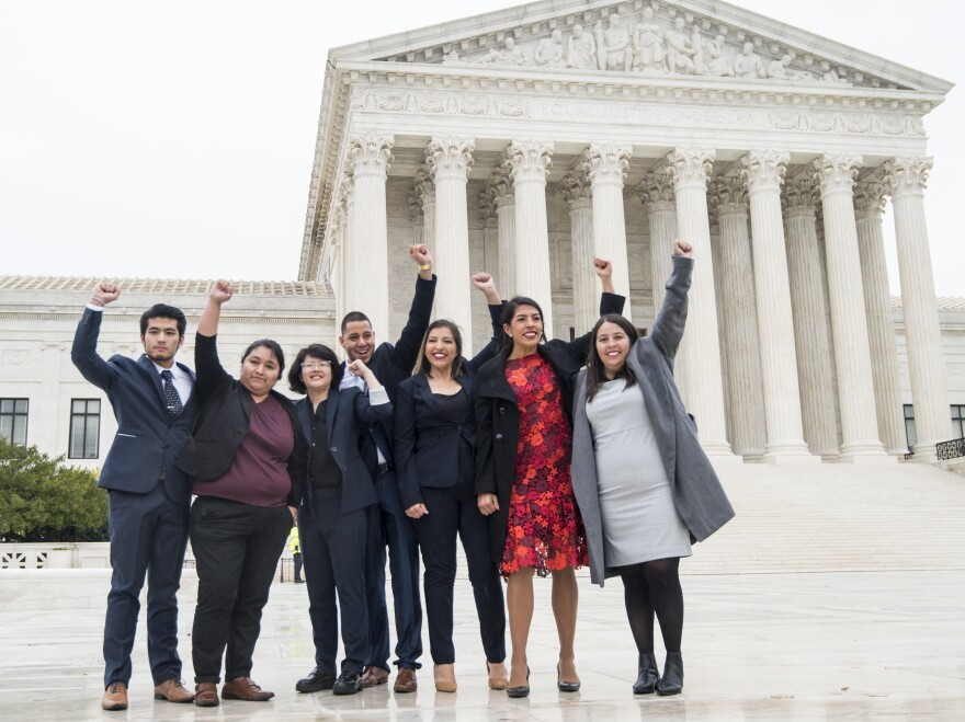 DACA recipients, including Carolina Fung Geng, (3rd from left), plaintiff Martin Batalla Vidal (center) and Eliana Fernández (3rd from right) hold their fists in the air as they enter the U.S. Supreme Court on Tuesday, Nov. 12, 2019.