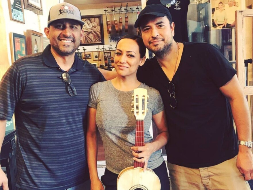From right to left: Candelas Guitars owner Tomás Delgado, musician and customer Stephanie Amaro and her husband, guitarist Andy Abad.