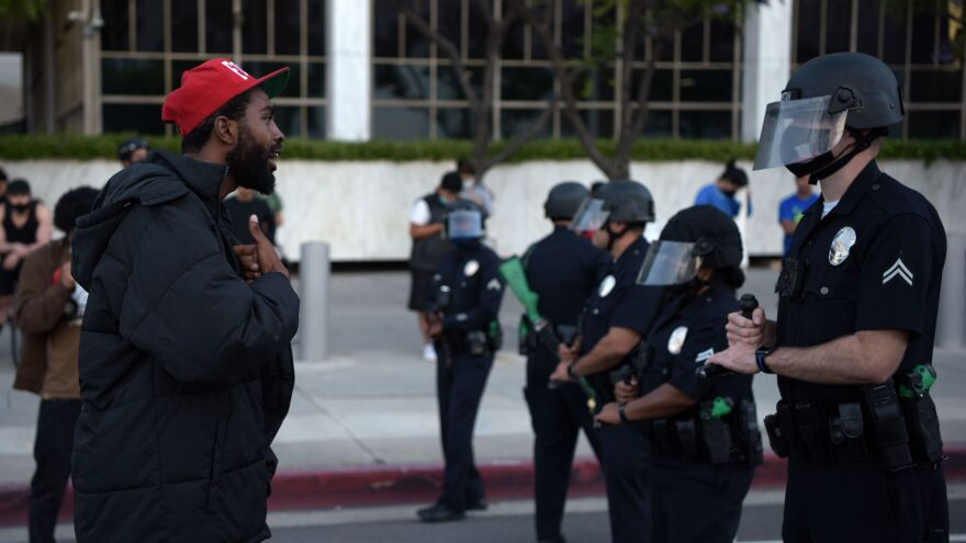 A demonstrator explains himself to an officer in riot gear during a protest Wednesday in downtown Los Angeles. The impact of Floyd's death has been felt well beyond Minneapolis' city limits.