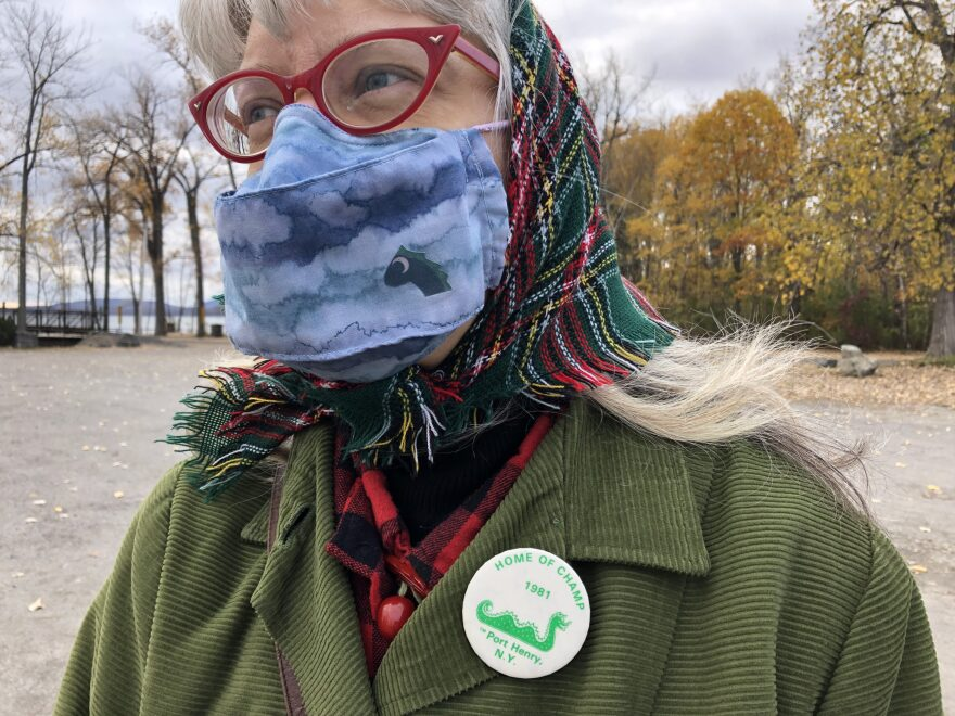 Andrea Anesi of Port Henry's Chamber of Commerce wears a homemade lake monster face mask and a Champ promotion pin from the 1980s. (Julia Press)