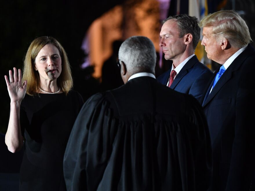 President Trump watches as Supreme Court Justice Clarence Thomas administers the constitutional oath to Amy Coney Barrett during a ceremony at the White House Monday evening.