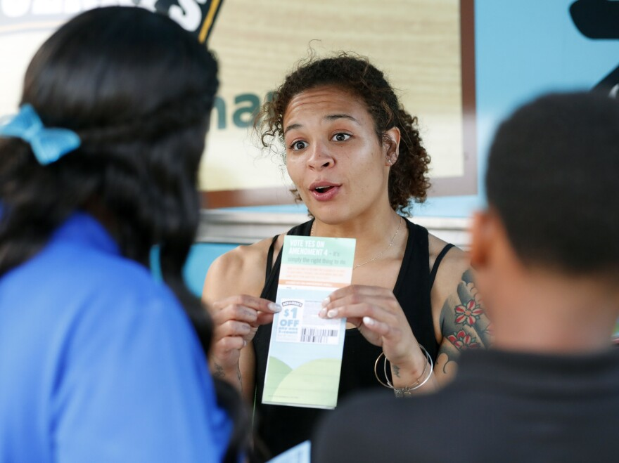 "Jessica Jones (center) speaks to people gathered around the Ben & Jerry's ""Yes on 4"" Truck about Florida's Amendment 4 initiative at Charles Hadley Park in Miami, on Oct. 22. Amendment 4 asked voters to restore the voting rights of people with past felony convictions."
