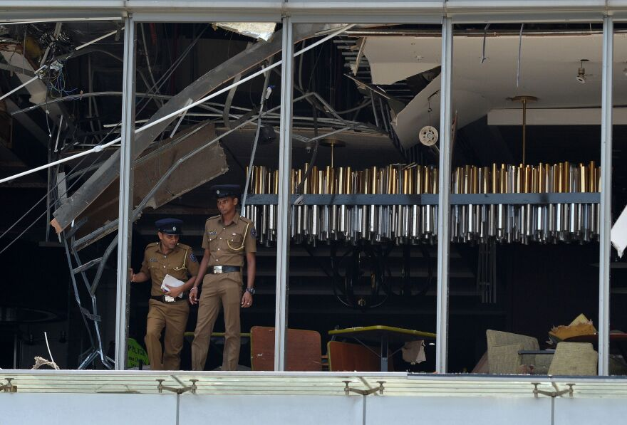 Sri Lankan police stand at the site of the explosion in a restaurant area of the luxury Shangri-La Hotel in Colombo.