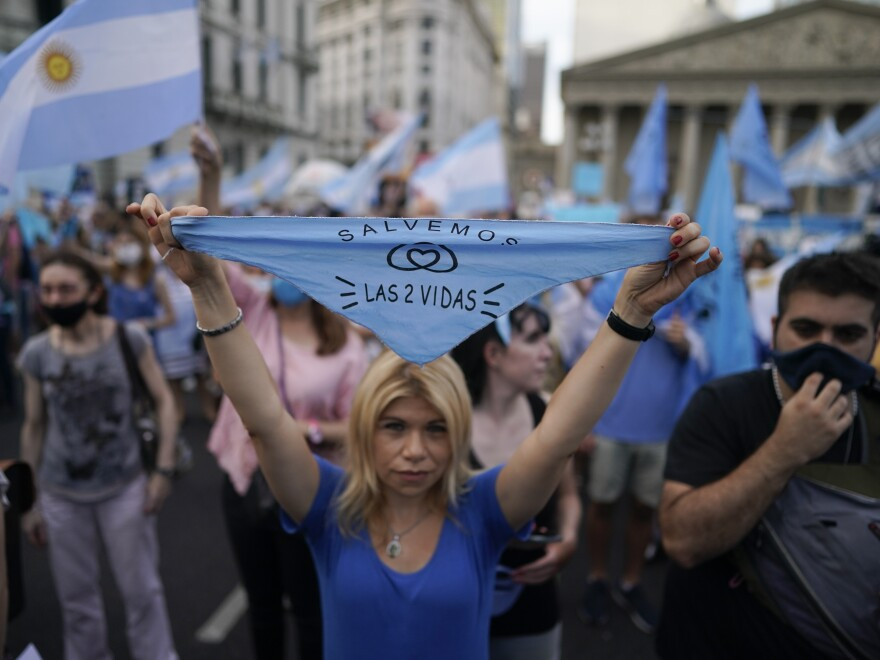 "An anti-abortion rights activist holds a handkerchief with text in Spanish that reads, ""save both lives,"" as she protests against the decriminalization of abortion on Monday at Plaza de Mayo in Buenos Aires, Argentina."