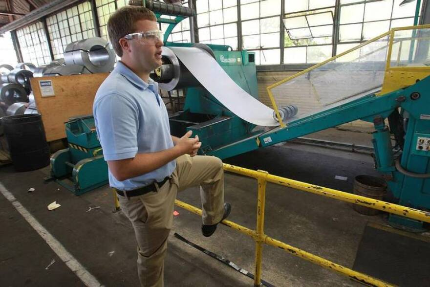 This 2017 file photo shows Nick Bauer, president of Empire Comfort Systems in Belleville, talking about a shear machine that cuts huge rolls of sheet metal to length for manufacturing gas heaters.