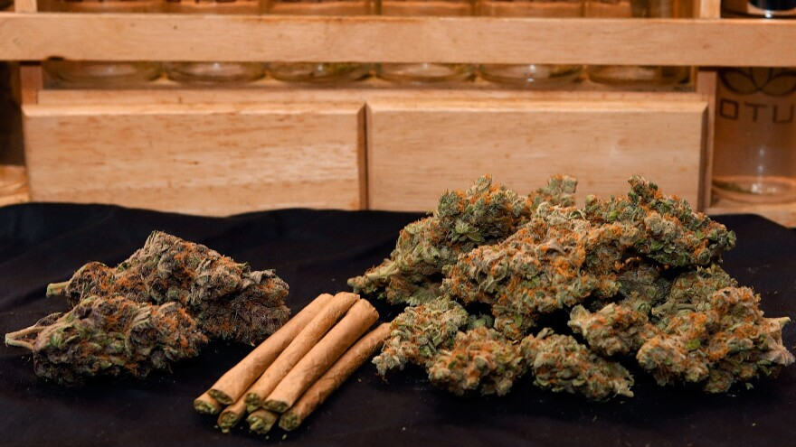 Colorado lawmakers approved two taxes on marijuana — a 15 percent excise tax, and a 10 percent sales tax. A photo depicts a quarter of an ounce, left, and one ounce of marijuana, along with a handful of rolled joints at a Denver dispensary.