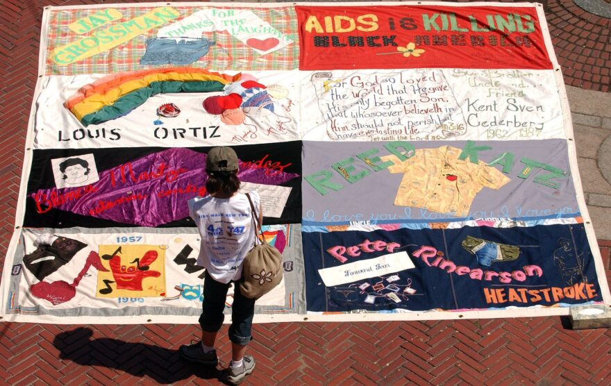 A woman looks at a quilt dedicated to those who lost their battle with AIDS at in Central Park, New York City.