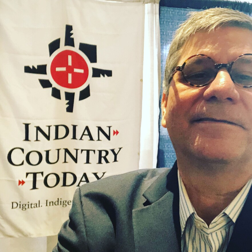 Mark Trahant stands in front of an Indian Country Today banner.