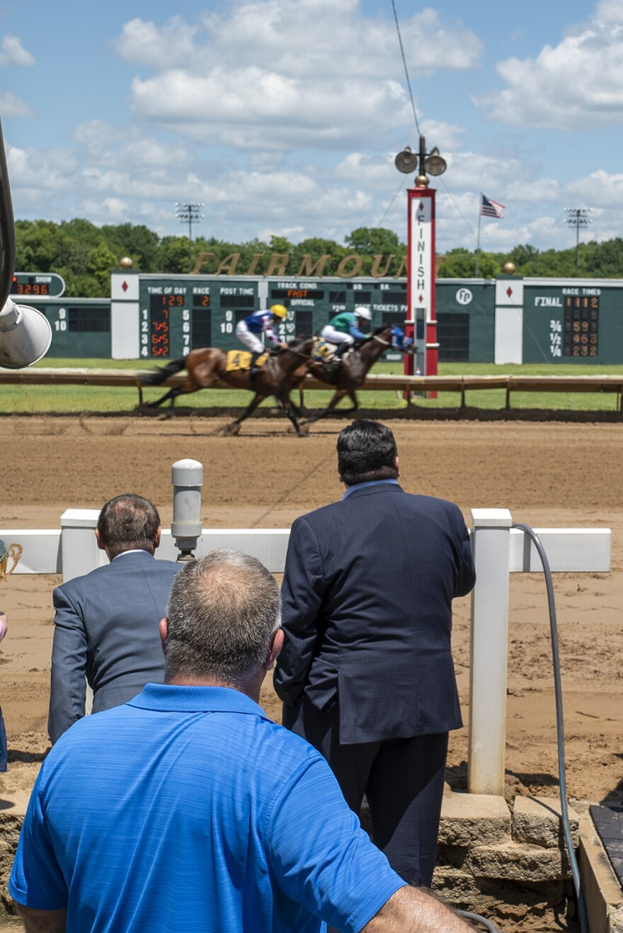 Gov. J.B. Pritzker watches horses cross the finish line at Fairmount Racetrack on July 30.
