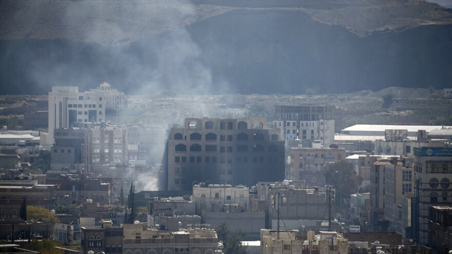 Smoke billows behind a building in the Yemeni capital Sanaa on Sunday, during clashes between Houthi rebels and supporters of Yemeni ex-president Ali Abdullah Saleh.