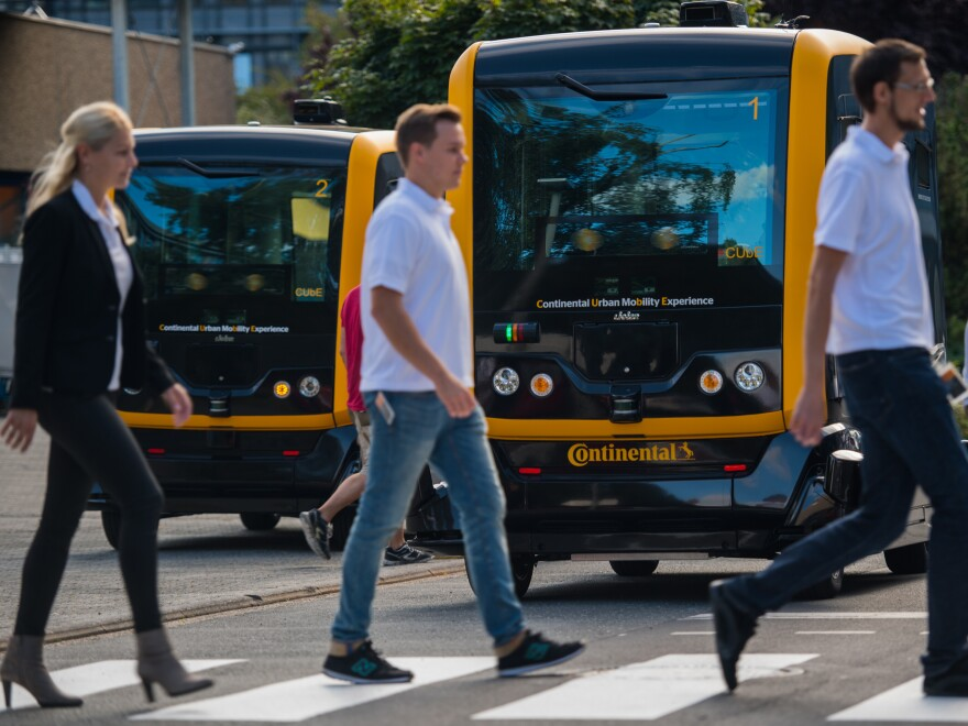 New research explores how people think autonomous vehicles should handle moral dilemmas. Here, people walk in front of an autonomous taxi being demonstrated in Frankfurt, Germany, last year.