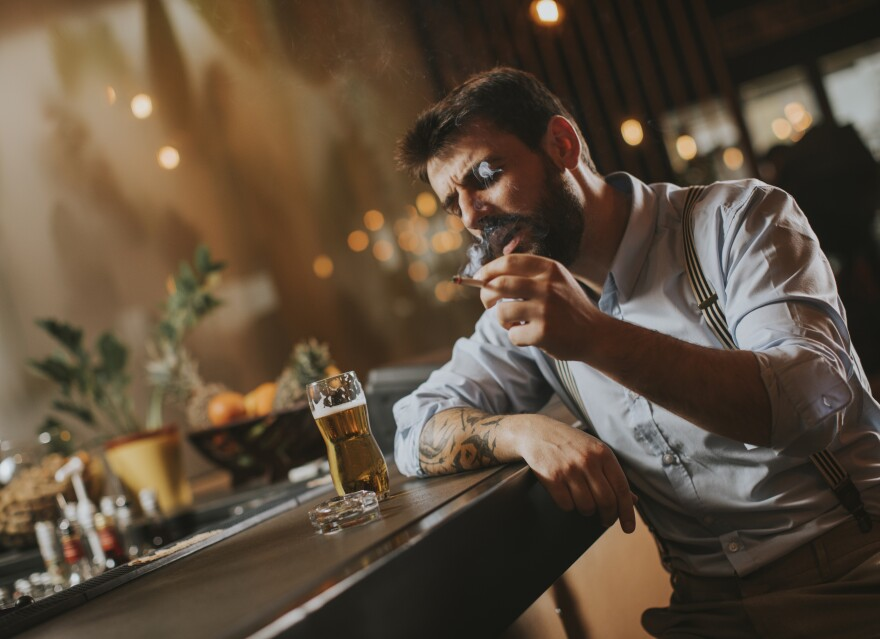Man drinking beer and smoking cigarette at pub