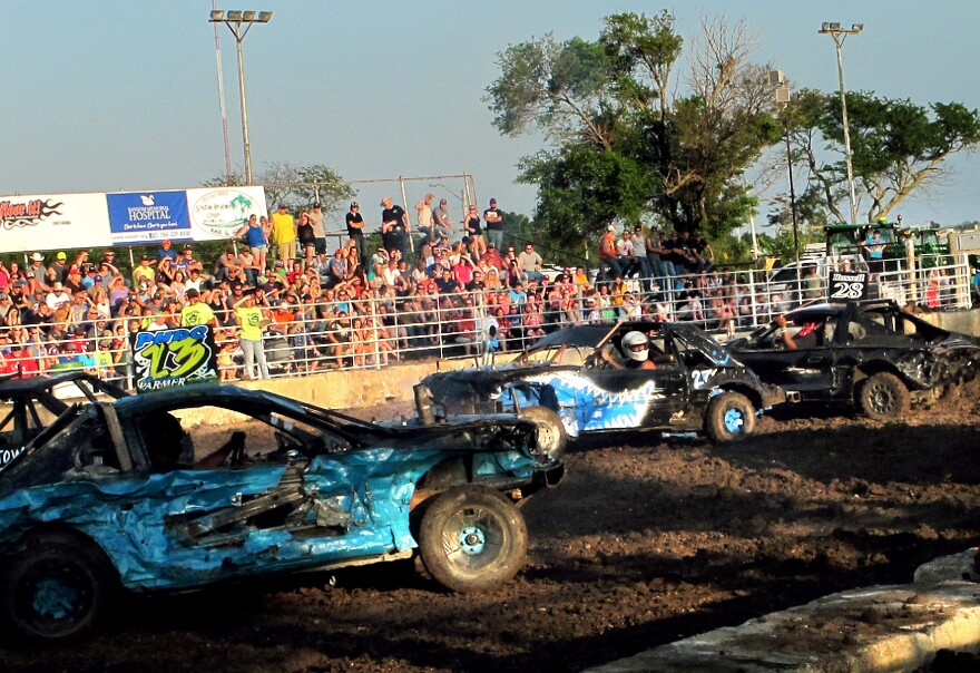 Travis Moyer (center) drives the car that he built for the demolition derby in Kansas.