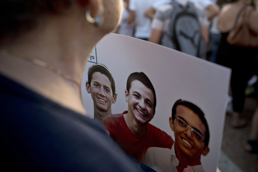An Israeli woman holds a poster with photos of three Israeli teens, who were killed in the summer of 2014.