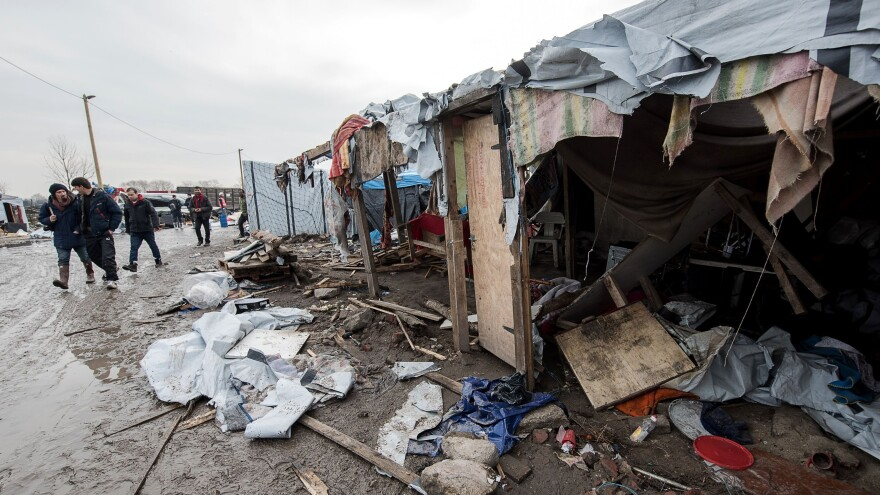 """People walk in the southern part of the so-called """"Jungle"""" migrant camp in Calais, northern France, which is being dismantled, on March 10, 2016."""