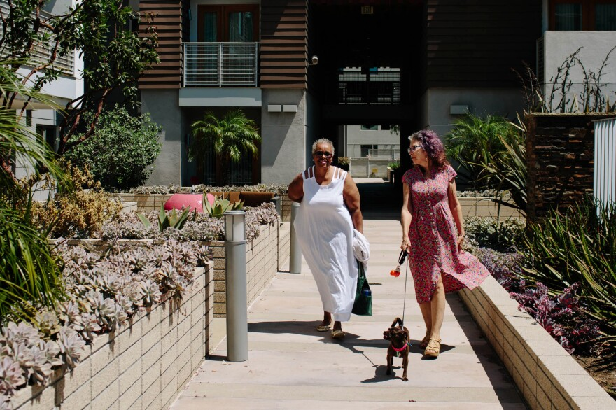 Bryant walks with Cohen and Cohen's dog, Penny, through the breezeway of the Long Beach Senior Arts Colony. Both women feel lucky to live in this creative community, but what worries them most now is how they'll manage if there's another rent increase.