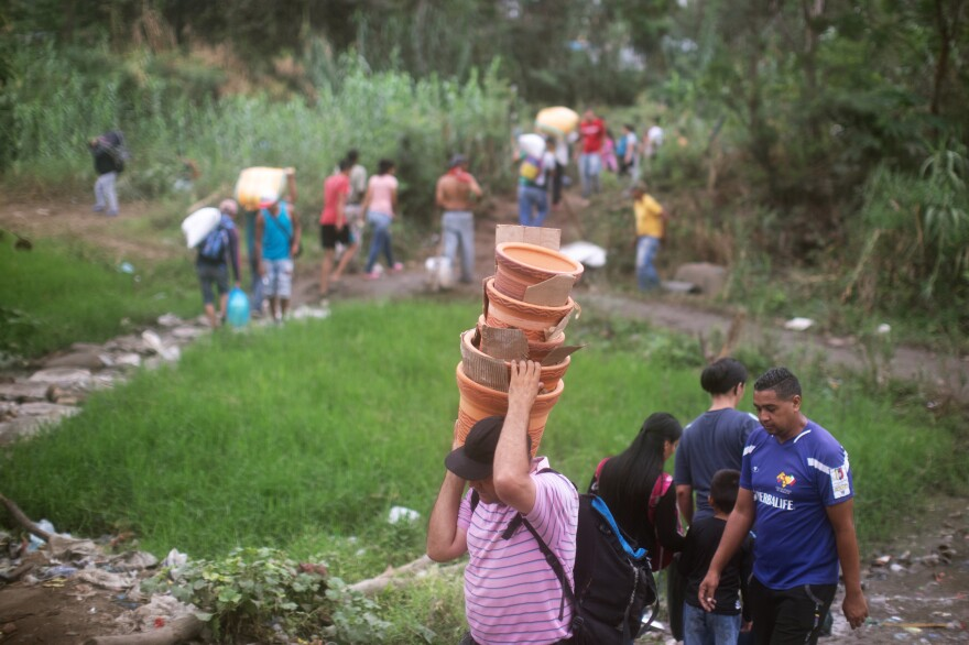 People walk from Venezuela to Colombia through an unauthorized border crossing recently in Villa del Rosario, Colombia. Many people are leaving Venezuela by foot.