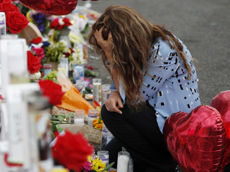 Gloria Garces kneels Tuesday in front of crosses at a makeshift memorial near the scene of a mass shooting at a shopping complex in El Paso, Texas.