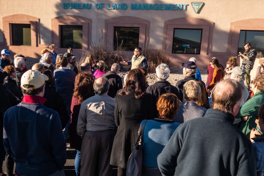 A Bureau of Land Management official addresses a crowd in front of his office building.
