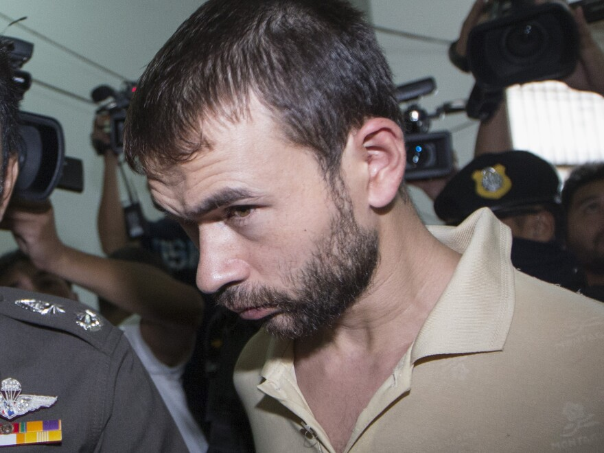 The suspect identified as Adem Karadag, arrested at an apartment last week and found with evidence police said included bomb-making equipment. He appeared in court in Bangkok on Saturday to extend his detention. Police now say he does not appear to be the man behind the bombing.