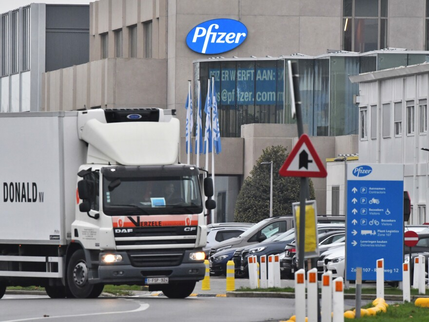 The U.K. will begin a mass vaccination against COVID-19 on Tuesday, as hundreds of thousands of doses of Pfizer's vaccine reach the public. Here, a temperature-controlled cold storage truck leaves a Pfizer facility in Belgium Thursday.