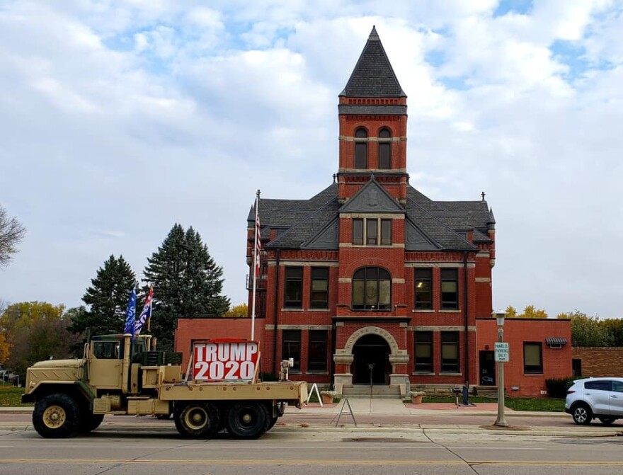 A military-style truck with campaign flags is parked outside the Monona County Courthouse.