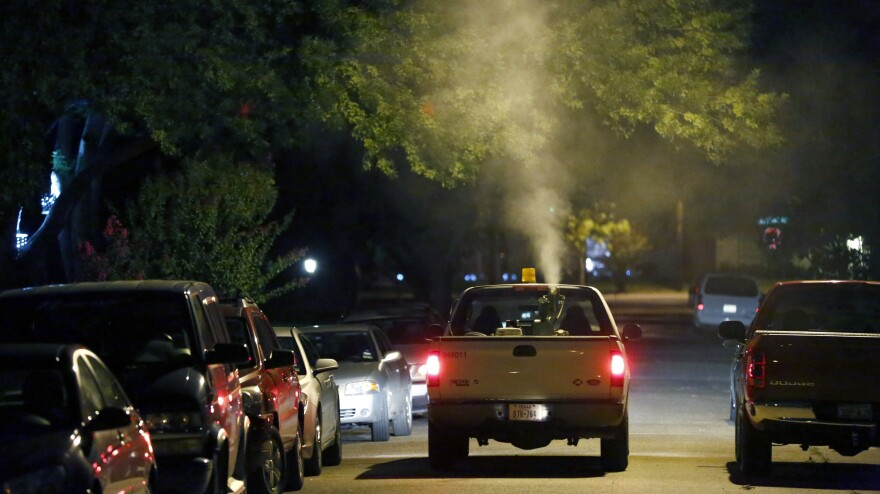 A sprayer truck blankets a neighborhood in North Dallas with insecticide to curb mosquitoes carrying West Nile virus in July 2012.