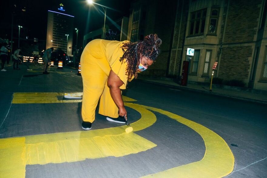 "San Antonio poet laureate Andrea ""Vocab"" Sanderson paints the words of her poem on downtown streets."