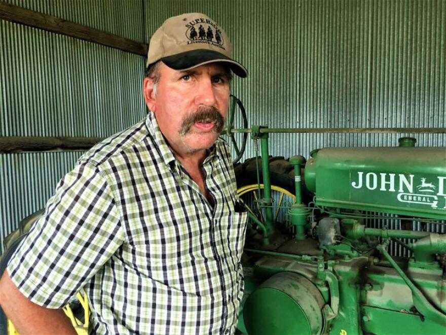 Duane Hund, who farms in the Flint Hills of Kansas City, stands next to a 1937 John Deere tractor. His grandfather bought it for $600 and traded four mules, Hund says.