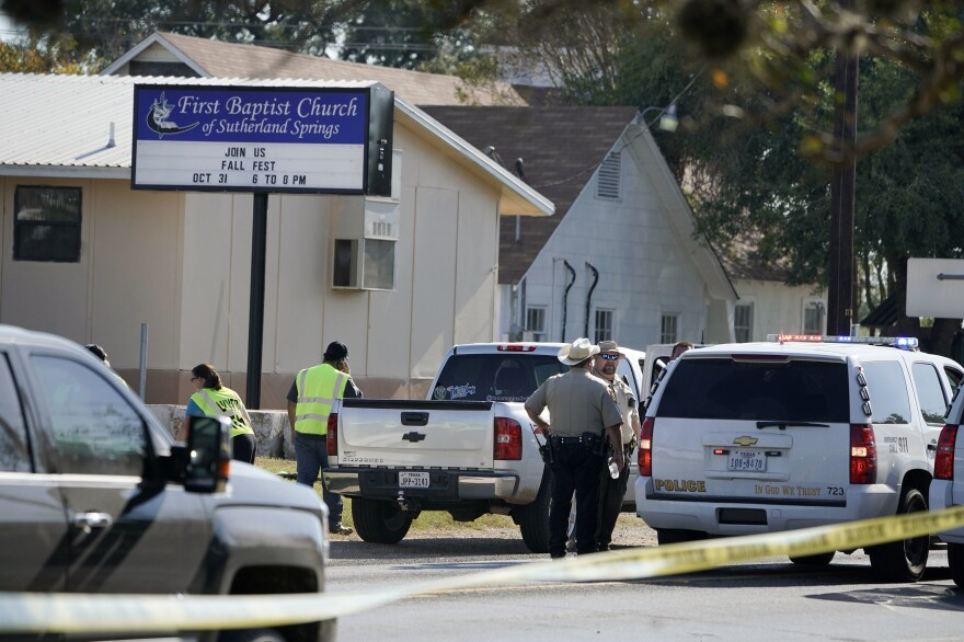 Law enforcement officers gather in front of the First Baptist Church after a fatal shooting Sunday in Sutherland Springs, Texas.