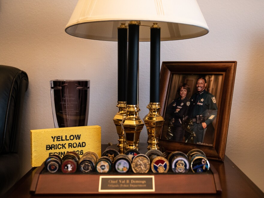Challenge coins from various law enforcement agencies sit in Rep. Val Demings' office. Students at the FBI National Academy receive the yellow brick after completing a grueling fitness challenge.