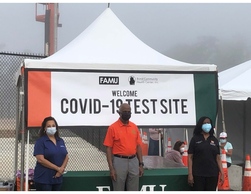"""Three people stand in front of a tent. On the tent is a banner that reads, """"COVID-19 Test Site."""""""