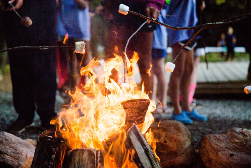 Cooking s'mores around a campfire.